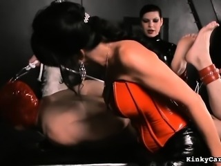 Latex clad nasty mistresses tie up their slave and make him suck a dildo