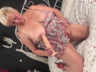 Horny grandma sucks a dildo before ramming her wet cunt