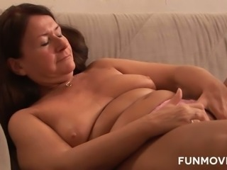 Dark haired nasty granny lies on sofa and pleases her flaccid kitty with...