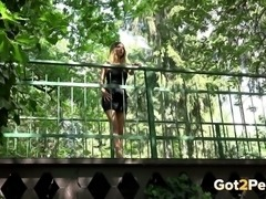 Hot blonde summer girl crouches on the bridge and pisses