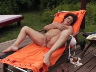 Fat mature bimbo enjoys fingering her cunt in the sun