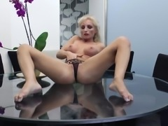 Luscious blonde cougar Kira gets up on the table to masturbate