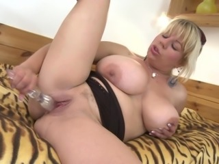 Busty mature chick with sunglasses takes the glass toy and has fun