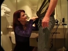 Redhead cutie sucking on a long shaft in the toilet