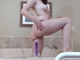 This hot redhead has no problem riding her dildo in the bathroom