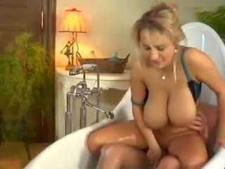 Bosomy blonde mommy takes a ride on a cock in a bathtub