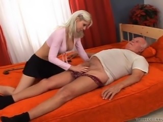 Grandpa lays on his back, dreaming about the old times, when he used to fuck naughty whores. He loved the communist regime, but now he's an old fart in a different era. Well, Grandpa gets a taste of the capitalism, as this young cute blonde has a taste of his dick! Look at her, sucking his saggy weenier!