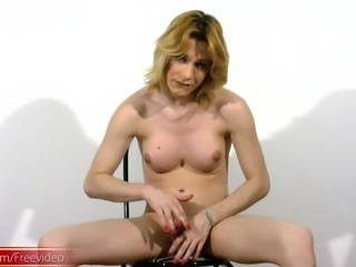 Kinky blonde tranny strips on a chair before jerking off