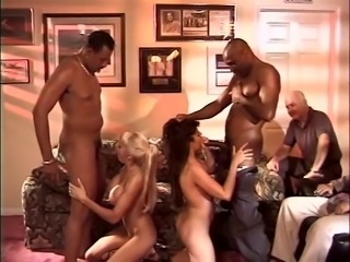 Two babes ride massive tools while being watched by a kinky fellow