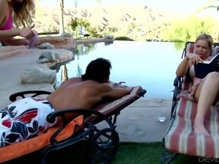 Beautiful blonde young chick blows a big white cock by the pool