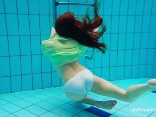 Redhead European teen having her small tits displayed underwater