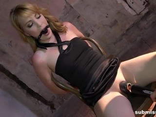 The blonde milf was tied up to a chair in the dungeon and the cruel master dominated her through out the session. Her moans could not break away from the beautiful pink lips, as the master closed her mouth with ball gag. He placed a vibrator on her clit and the wet pussy started leaking sticky juices.