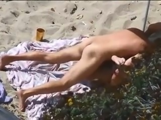 Tanned dark haired slutty bitch was topping her man's dick on the beach