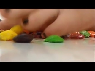 Girl crushes candies with her feet