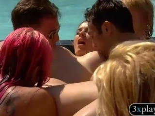 Group of swingers having fun doing oral sex by the pool