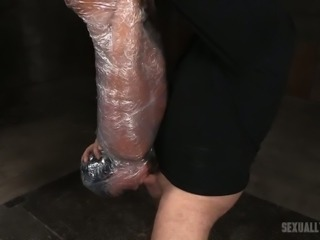 Brunette poor girl wrapped in plastic and suspended upside down