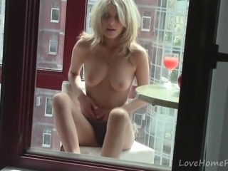 Blonde hottie loves touching herself by the window