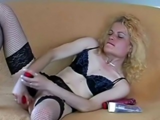 A hot blonde slut in a sexy lingerie fucks he ass and pussy with dildo