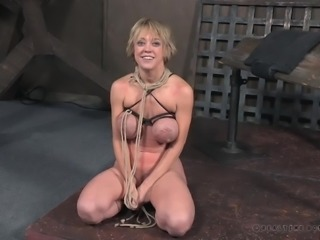 Hot blonde momma Dee Williams gets more than she bargained for, when she agreed to try the BDSM scene. Her big tits looking even larger in leather ties, she lies back with her hands tied, her hairless pussy deeply penetrated by the sybian, she's riding. A thin whip slides across her trembling belly.