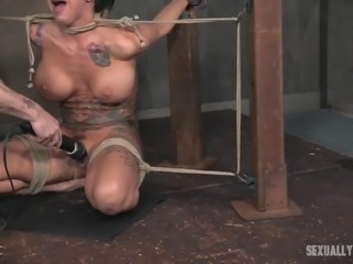 She is constrained and not going anywhere, so the two master gang up on her and use their cocks in ways that humiliate her. One master face fucks her, while the other gets jerked off. She is taking that cock so deep.