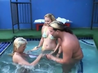 Frisky blonde sluts give dude a handjob in the pool
