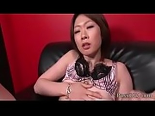 Rio Kagawa is squeezing her tits and playing with her pussy on a black leather c