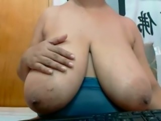 Mature black woman shows giant natural balloons on webcam