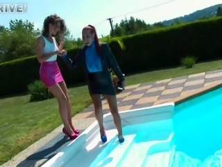Dressed women hook up for a lesbian shag in a swimming pool