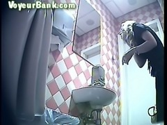 Cute blonde white chick in black pants pisses in the toilet