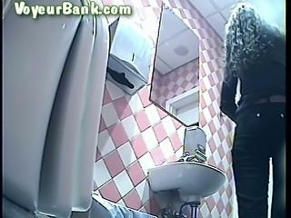 Curly haired white sweetheart filmed from behind in the toilet