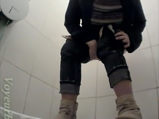 White chick in warm clothes pisses in the toilet room and wipes her pussy