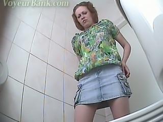Chunky white stranger chick in denim skirt pisses in the toilet