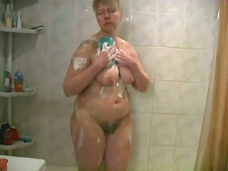 Chunky blonde cougar with hairy pussy and big breasts washes in the bathroom