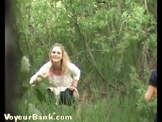 Blonde sweet sexy girl in the high grass pisses while her friend waits