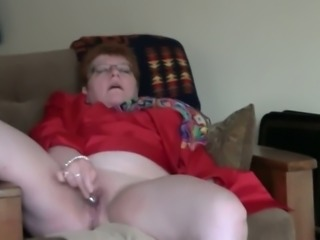 Short haired nerdy granny in red jacket masturbates her mature cunt