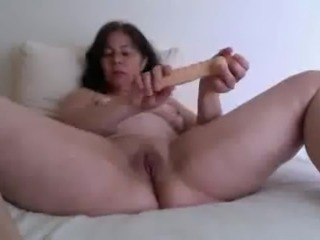 Masturbating MILFie housewife flashes her own natural tits on bed