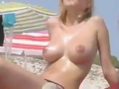 Nice video of amateur pale blonde sunbathing topless on the beach
