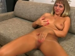 Tanned and naturally buxom light haired lady plays with boobs and clit