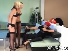 Strapped guy smothered by a couple of rough dominas