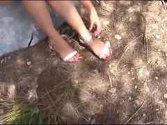 stinky teen feet with dirty soles in the woods with sandals