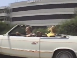 Blonde chick flashes tits in convertible car public road