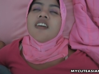 Cute and young Asian wife in hijab pleases her man