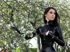 Sultry brunette babe shows off her sexy latex suit outside