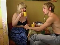 Auntie And Nephew Having Coffeebreak In Kitchen