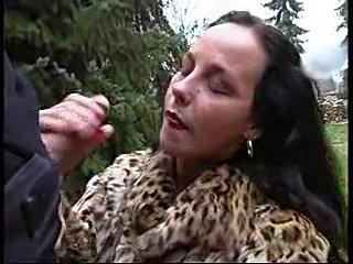 Chick in fur coat giving handjob outdoors
