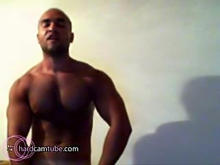 Muscular stud shows off his ripped abs and strokes his huge cock