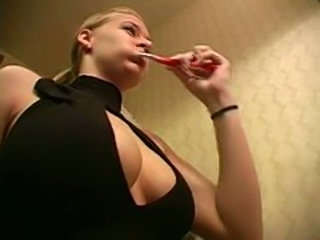 Sexy blonde showing her cleavage while brushing her teeth
