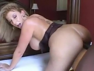 Sara Jay playing with a large black sausage