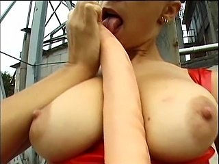 Busty redhead MILF with amazing tits playing with a big toy outdoor