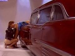 Classic scene with slut bent over a car